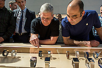 Tim Cook, chief executive officer of Apple Inc., looks at Apple Watches on display at an Apple Inc. store in Palo Alto, California, U.S., on Friday, April 10, 2015. From London to Beijing, Apple stores saw few customers lined up before opening Friday as pre-orders started. The first new gadget under Chief Executive Officer Tim Cook is selling in eight countries and Hong Kong, with shipments scheduled to start April 24. Photographer: David Paul Morris