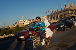 Syria.<br /> A Syrian couple riding in a motorcycle with a dozen cars and even more motorcycles celebrating a local wedding by shooting in the air and blowing the horn. (location not shown for security reasons), <br /> Sunday, 16th June 2013<br /> Picture by Daniel Leal-Olivas / i-Images