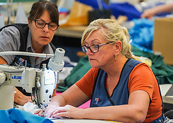 © Licensed to London News Pictures. 21/04/2020. Dukinfield, UK.   A woman stiches medical clothing as staff at Tibard begin working around the clock an order of 5,000 units of nurses uniforms (scrubs) for NHS workers per week in Dukinfield , owing to growing demand during the COVID-19 pandemic. The factory typically manufactures uniforms for the catering industry.  Photo credit: Ioannis Alexopoulos /LNP