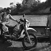 """Digby (C) and Noel (L) load a motorbike onto a """"bomb boat"""" to cross the Senphen tributary of the Bangphai River, outside the """"bomb village"""" of Ban Senphen. The village is located in the Ban Phanhop valley, one of the """"chokes"""", or narrow corridors along the Ho Chi Minh Trail in Laos that were heavily bombed by American forces during the Vietnam War. Much of the village infrastructure, from housing supports to boats, are constructed from the metal from downed airplanes and unexploded bombs."""