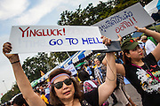 24 NOVEMBER 2012 - BANGKOK, THAILAND:  Women carry placards in opposition to Thai Prime Minister Yingluck Shinawatra during a large anti government, pro-monarchy, protest  on November 24, 2012 in Bangkok, Thailand. The Siam Pitak group, which sponsored the protest, cited alleged government corruption and anti-monarchist elements within the ruling party as grounds for the protest. Police used tear gas and baton charges againt protesters.       PHOTO BY JACK KURTZ
