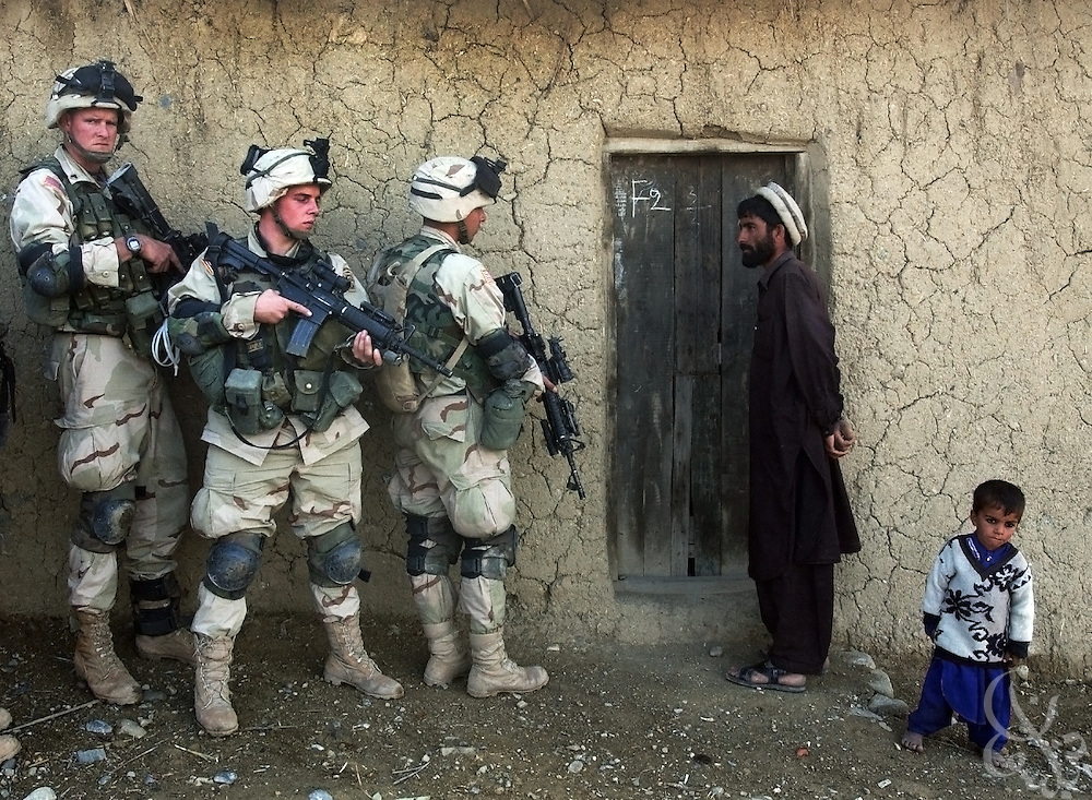 An Afghan man and his son watch as soldiers from the U.S. Army 82nd Airborne Division prepare to sweep their home November 7, 2002 in southeastern Afghanistan. Soldiers discovered over a dozen mines and grenades, 14 rocket propelled grenades, and plastic explosives as they searched several compounds as part of Operation Alamo Sweep. This house contained no weapons.