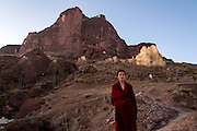 A monk stands for a portrait in front of a holy mountain, at the base of which Rabgya monestary is located. The monestary is home to around 500 monks of the Gelukpa sect.