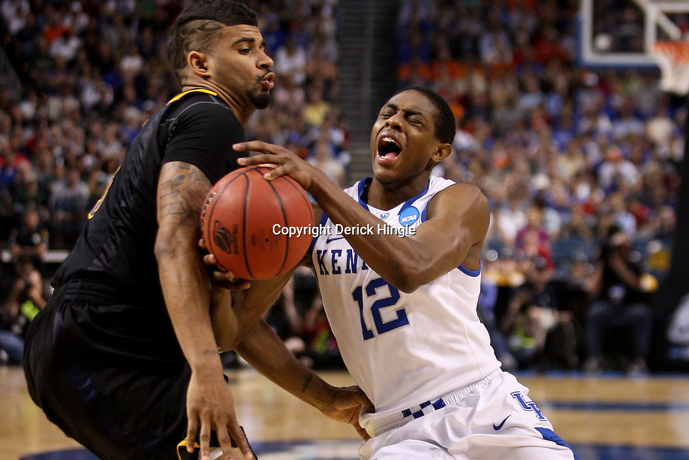 Mar 19, 2011; Tampa, FL, USA; Kentucky Wildcats guard Brandon Knight (12) draws a foul from West Virginia Mountaineers guard Casey Mitchell (3) during the second half of the third round of the 2011 NCAA men's basketball tournament at the St. Pete Times Forum. Kentucky defeated West Virginia 71-64.  Mandatory Credit: Derick E. Hingle