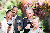 Two couples holding wine outdoors, portrait