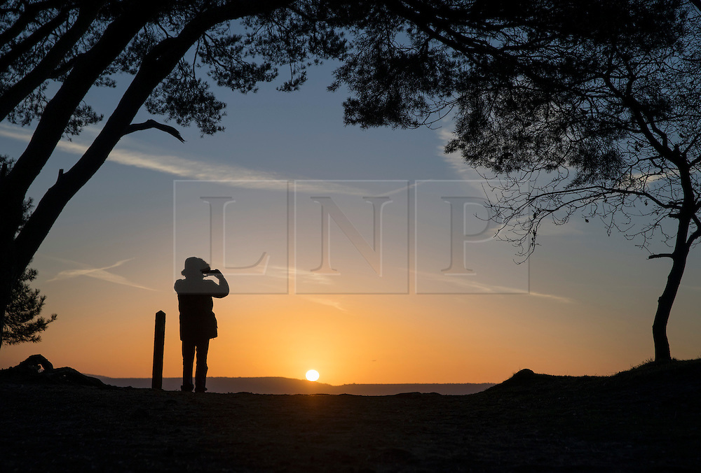 © Licensed to London News Pictures. 05/01/2017. Chilworth UK.  A visitor to St Martha's Hill in the North Downs takes a photograph at sunrise.  A continuing cold spell has seen temperatures as low as -6 in some areas. Photo credit: Peter Macdiarmid/LNP