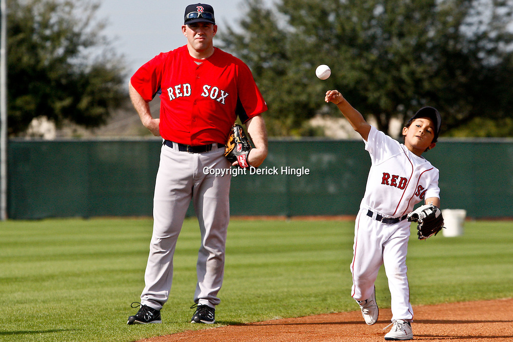 February 17, 2011; Fort Myers, FL, USA; D'Angelo Ortiz son of Boston Red Sox first baseman David Ortiz (not pictured) tosses the ball and third baseman Kevin Youkilis watches during spring training at the Player Development Complex.  Mandatory Credit: Derick E. Hingle