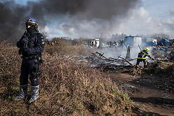 Licensed to London News Pictures. Calais, France. 03/03/16.  A fireman extinguishes a blaze that brought down a shelter used by refugees. French authorities are clearing the southern half of the Calais 'Jungle' camp, which charities estimate to contain 3,500 people.. Photo credit : Rob Pinney/LNP