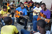 Instructor Fitrion Junior (center) leads a strumming exercise on the patio in Jacmel, Haiti. Guitar is one of the largest classes at the school.