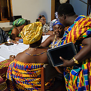 Queen Mothers, traditional female leaders, discussing the order of events ahead of a swearing-in of new members of their council in Accra, Ghana on 23 June 2015. Their roles are evolving, with formal legislative and governmental recognition now underpinning their position in their communities.