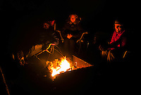 Group of friends sitting around a camp fire.