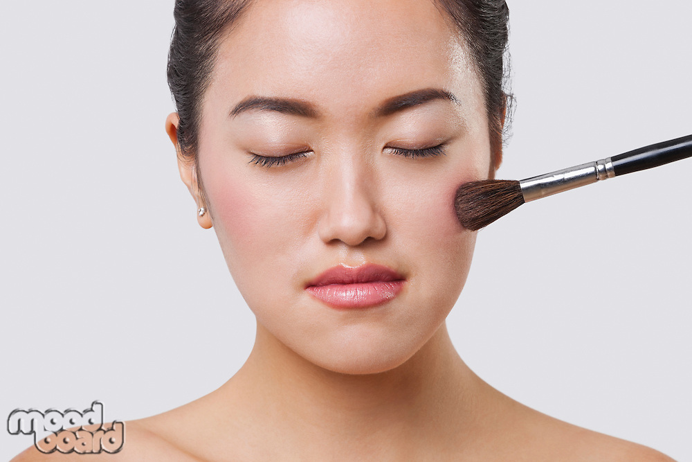 Close-up of young woman applying blush over white background