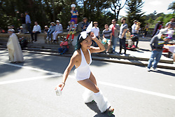"""A roller skating woman carrying """"boxed water"""" maneuvers around Golden Gate Park during the 105th running of the Bay to Breakers 12k, Sunday, May 15, 2016 in San Francisco. The 7.42-mile race from San Francisco Bay to the Pacific Ocean, which attracts a field of tens of thousands of runners, from elite runners to weekend warriors, some clad in costume and some in nothing at all. (Photo by D. Ross Cameron)"""