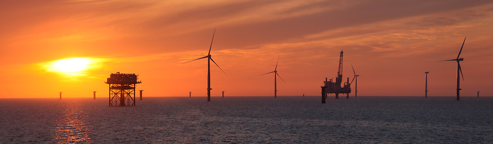 © Rob Arnold.  01/04/2014. North Wales, UK. A bright orange sky at sunset over the Gwynt y Môr Offshore Wind Farm off the coast of North Wales. The installation jack up barge, Sea Worker, can be seen in the distance. Photo credit : Rob Arnold
