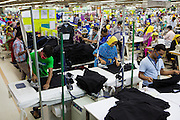 Garment workers ironing and stitching inside an Epyllion Group garment factory in Bangladesh.
