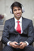 Young Indian businessman listening music on headphones
