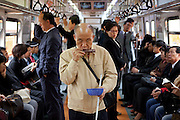 Blinder Mann mit einer Mundharmonika musiziert in der Metro in Seoul zwischen anderen Reisenden um sich etwas zusaetzliches Geld zu verdienen. <br />