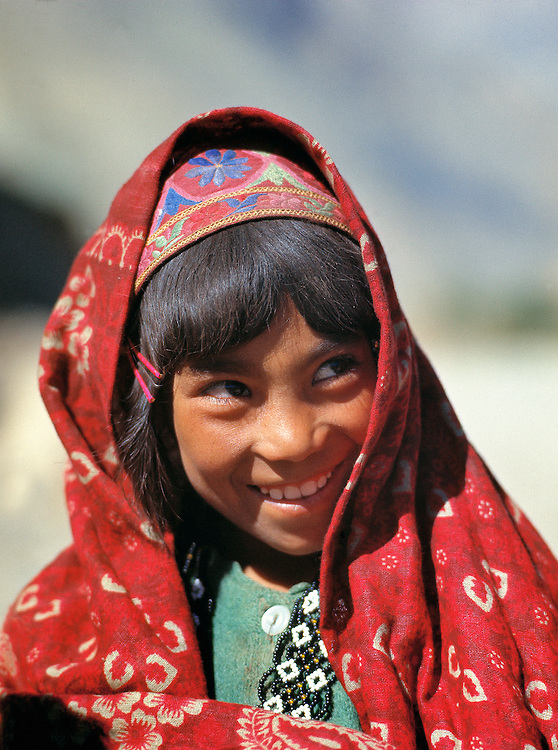 A young girl glances at her sister with smiling eyes, on the Shibar Pass in Afghanistan.