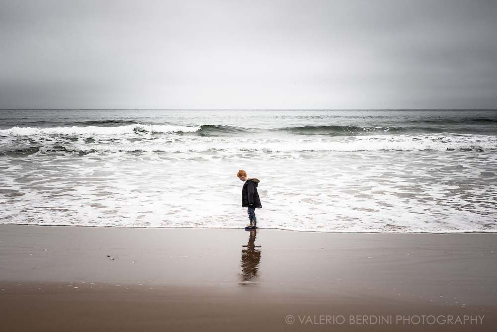A young, red-headed boy walks on the foreshore of a beach on the Northern Irish coast waiting for a wave to touch his wellies.
