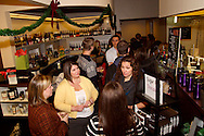 Members of Generation Dayton talk as they check out wine and chocolate that goes with it during their annual holiday wine tasting at Winan's Chocolates and Coffees near the Dayton Mall in Miami Township, Thursday, December 1, 2011.