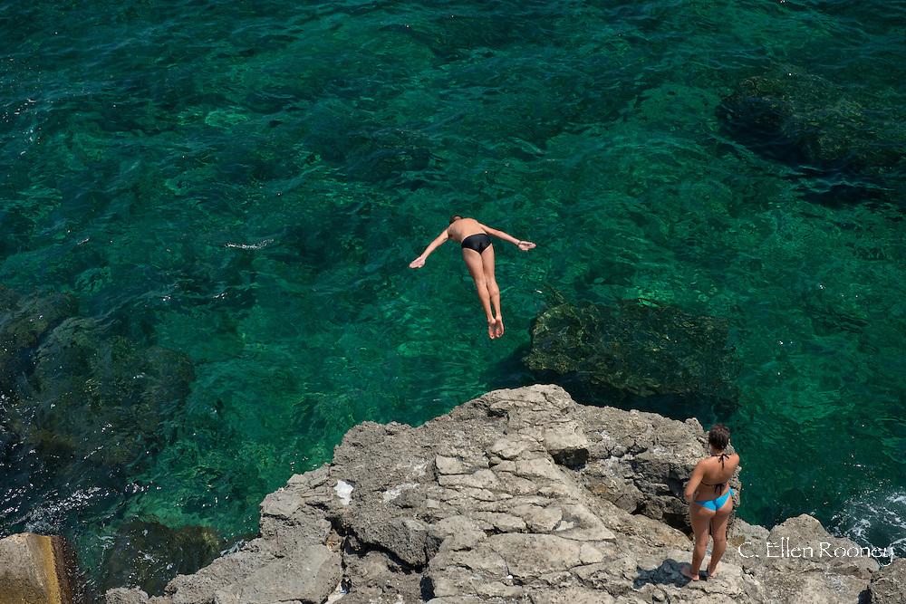 A swimmer diving into emerald seas in Ortigia, Syracuse, Sicily, Italy