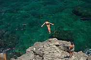 A swimmer diving into emerald seas in Ortigia, Syracuse, Sicily, Italy