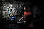 A young man working in a electrical generator repair shop. Un ragazzo lavora in un negozio specializzato nella riparazione di generatori elettrici.