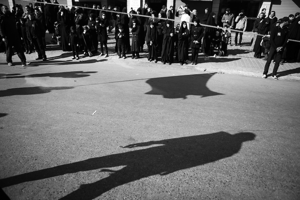 Spectators watch the long shadows of the mourners as they pass.