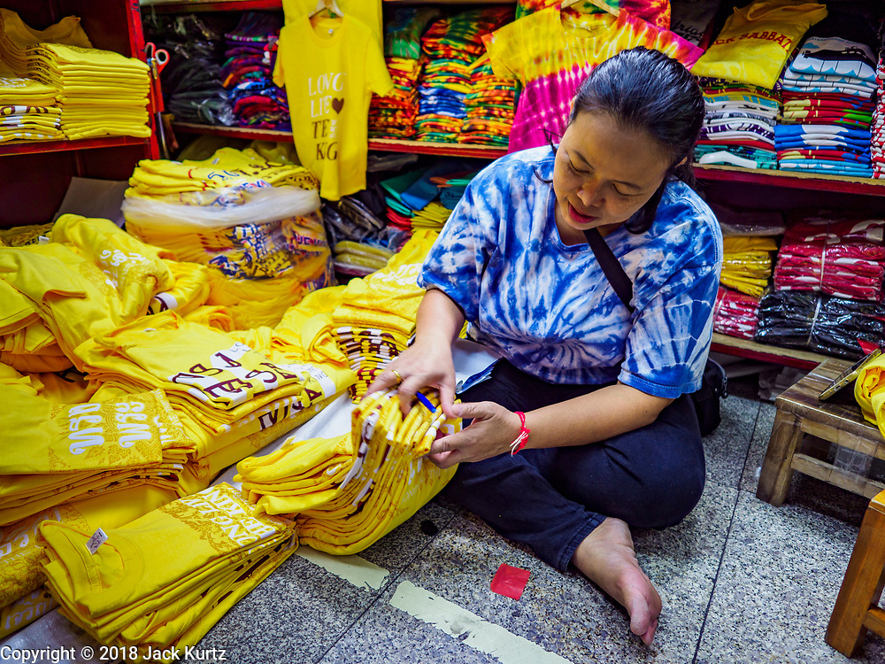 "03 JULY 2018 - BANGKOK, THAILAND: A shop keeper in Bobae Market in Bangkok inventories yellow shirts that say ""Long Live the King."" The birthday of King Maha Vajiralongkorn Bodindradebayavarangkun, Rama X, is 28 July. The King, the only son of Thailand's late King Bhumibol Adulyadej, became the King of Thailand in 2016 after the death of his father. King Vajiralongkorn was born on 28 July 1952, a Monday. In Thai culture each day of the week has a color, and yellow is the color is associated with Monday, so people wear yellow for the month before his birthday to honor His Majesty.     PHOTO BY JACK KURTZ"