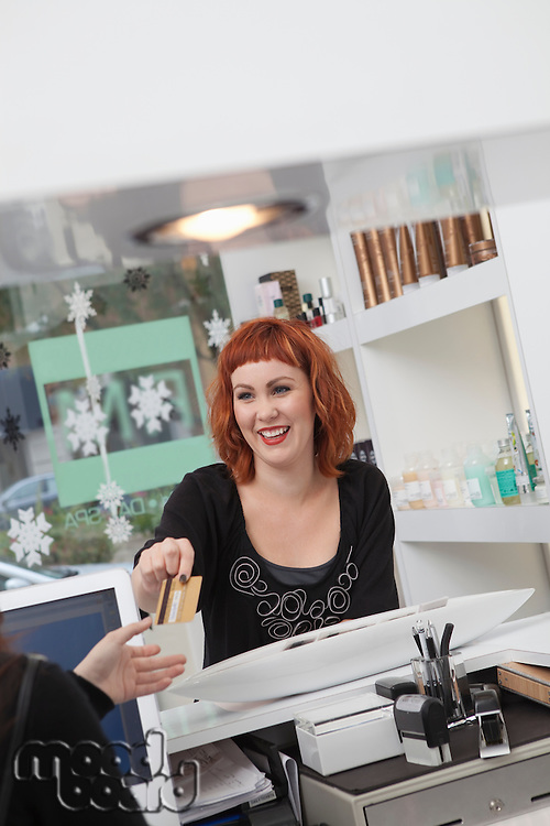 Owner / receptionist takes payment in hairdressing salon