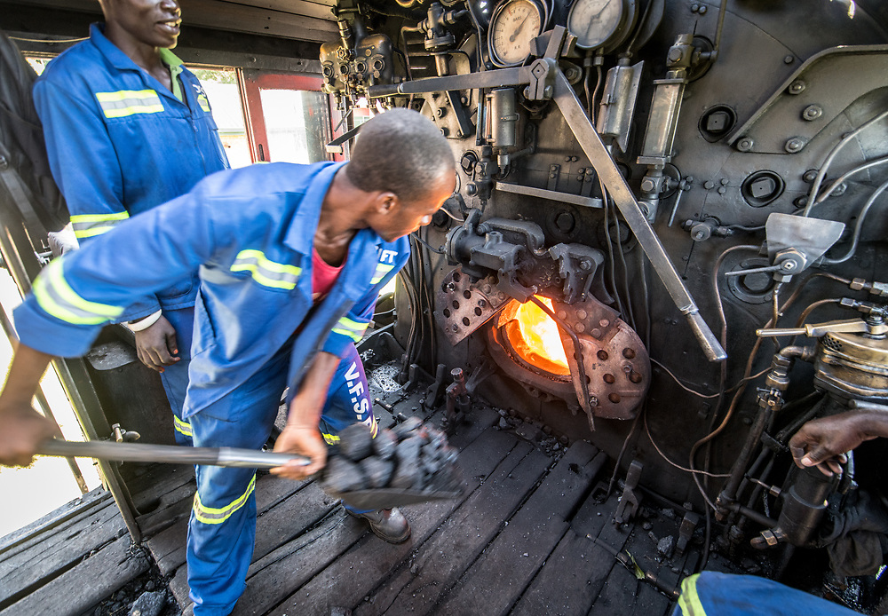 An adult male worker loads coal into the engine of a Garratt steam locomotive. Zimbabwe