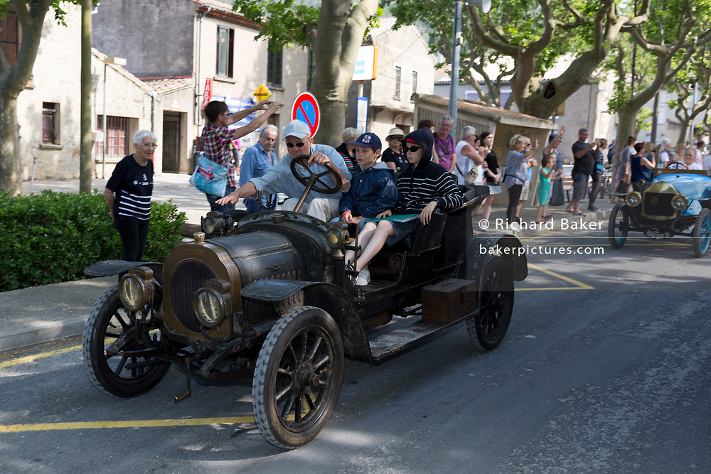 A visiting vintage car leaves a French village, during a three-day rally journey through the Corbieres wine region, on 26th May, 2017, in Lagrasse, Languedoc-Rousillon, south of France. Lagrasse is listed as one of France's most beautiful villages and lies on the famous Route 20 wine route in the Basses-Corbieres region dating to the 13th century.