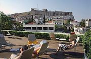 Griekenland, Athene, 5-7-2008Uitzicht op de stad en akropolis vanaf het dak van een hotel aan de voet van deze heuvel. Toeristen doen een dutje in de middagzon.Foto: Flip Franssen