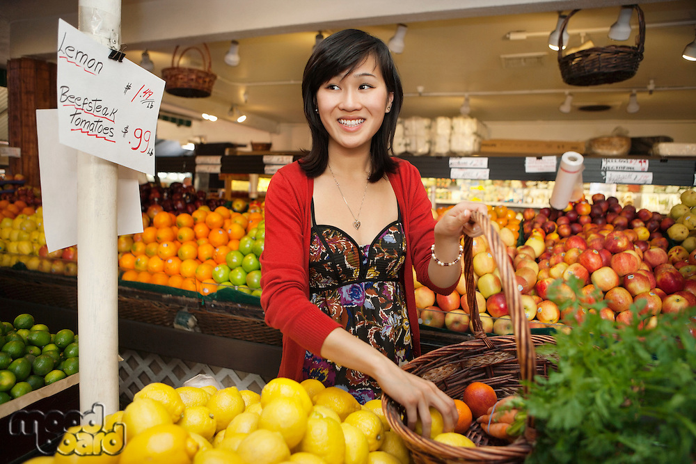 Happy young woman looking away while selecting lemon