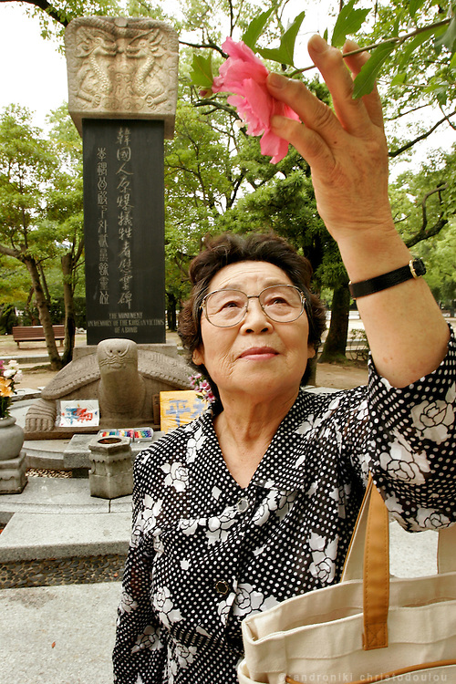 Ms Park Nam Joo. Korean Hiroshima A-Bomb survivor holding a Korean flower. At the Peace Memorial Park, In front of the monument for Korean victims of the A-Bomb on Hiroshima.