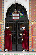 Two doormen dressed in red velvet capes at the entrance to La Mamounia Hotel in Marrakech, Morocco