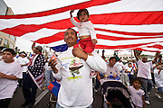 10 APRIL 2006 - PHOENIX, AZ: RUDOLFO MICHEL carries his daughter SHELLY MICHEL under an American flag during a march for immigrants' rights. Michel is an illegal immigrant from Jalisco, Mexico, his daughter was born in the US and is a US citizen. More than 200,000 people participated in a march for immigrants's rights in Phoenix Monday. The march was a part of a national day of action on behalf of undocumented immigrants. There were more than 100 such demonstrations across the US Monday. Protestors were encouraged to wear white, to symbolize peace, and wave American flags, to demonstrate their patriotism to the US.  Photo by Jack Kurtz