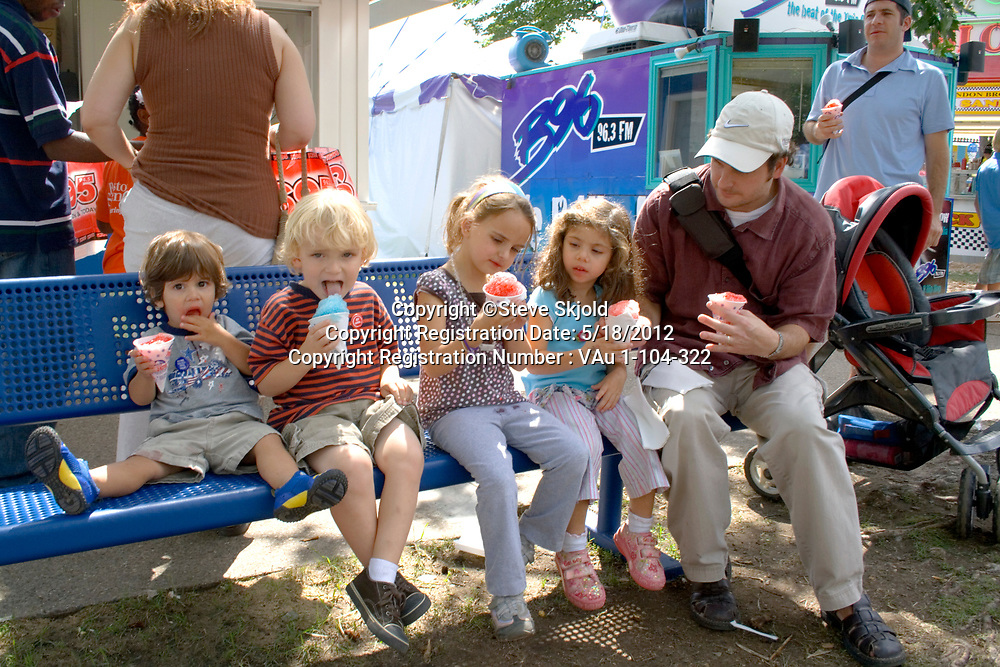 Four young children eating snow cones on bench with father. Minnesota State Fair St Paul Minnesota MN USA
