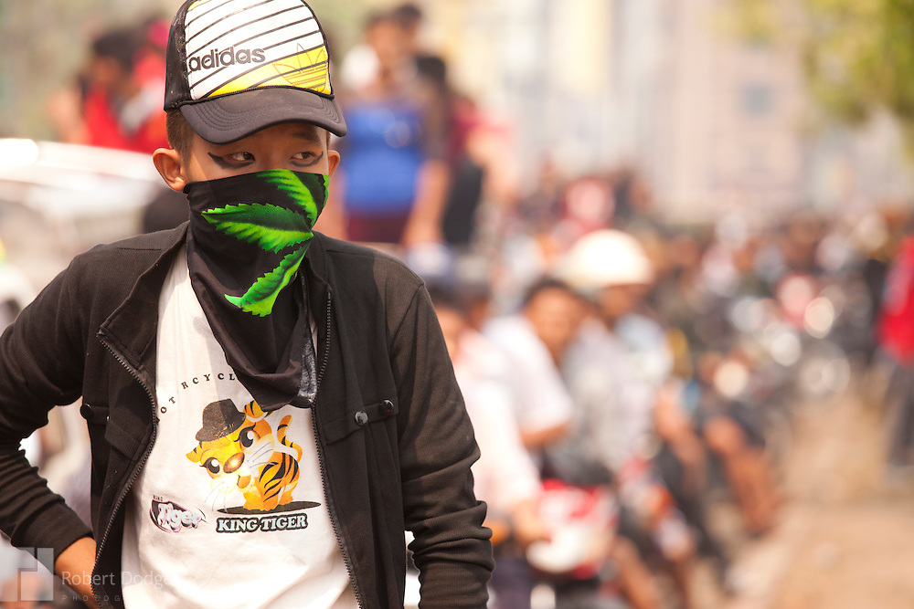Mandalay, Myanmar- April 14, 2013: This young man covered up to protect himself from the sun and vehicle exhaust as he waited out a traffic jam during Myanmar's Thingyan Water Festival. Thingyan is held in April, one of the hottest months of the year in Myanmar. The water festival marks the country's New Year celebration and the festival includes lots of drinking, singing, dancing and theater. Wherever you are you are likely to get doused with water as the Burmese see this as a cleansing of the previous year's sins and bad luck and a blessing for good luck and prosperity in the year ahead. In the major cities of Mandalay and Yangon, large platforms are erected along major roadways and are equipped with high powered water hoses. The platforms, sponsored by large corporate donors, also have dance stages and play the latest pop and hip hop music. Thousands of residents pour into the streets by foot, motorbike and flatbed truck to get hosed under the platforms while they drink and dance. Many of the young celebrants wear their best clubbing clothes. And many of the party goers are men, having left their wives and girlfriends at home.