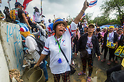 17 FEBRUARY 2014 - BANGKOK, THAILAND: A woman cheers while anti-government protestors build a cement wall around Government House during their retaking of the complex Monday. The anti-government protest movement, led by the People's Democratic Reform Committee and called Shutdown Bangkok has been going on for more than a month. The protest movement called, the People's Democratic Reform Committee (PDRC), wants to purge the current ruling party and its patrons in the Shinawatra family from Thai politics. The movement has consistently refused any dialogue or negotiations with the Pheu Thai ruling party. Over the weekend Thai police claimed to have taken the protest areas around Government House (the Prime Minister's office) away from protestors but on Monday protestors marched unimpeded to Government House and retook the area.   PHOTO BY JACK KURTZ