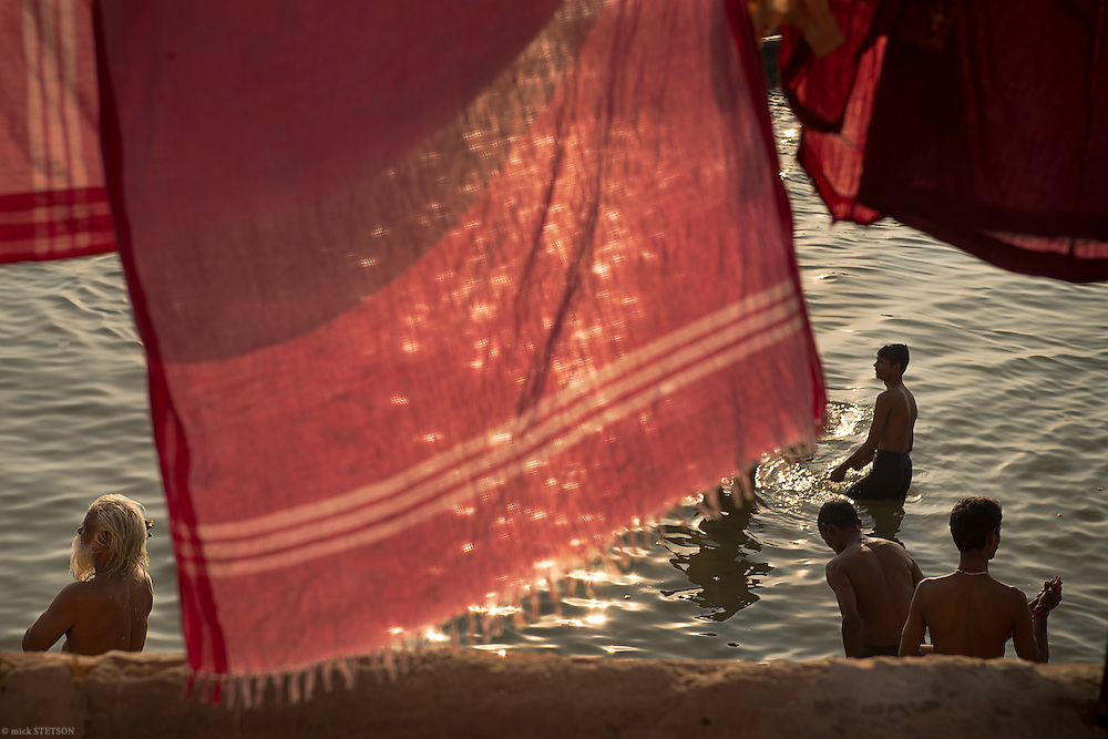 — During the eary hours of morning, bathers crowd the shallow shoreline waters of the Ganga, immersing in the Hindu metaphor and belief that the river flows unbroken from ancient times into the present.