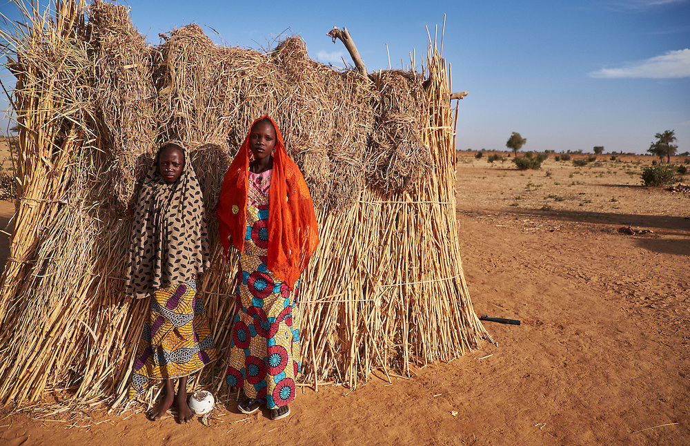Girls stand outside a shelter in a camp of internally displaced people by the side of the road on the highway outside of Diffa, Niger on February 14, 2016. Caritas undertook a distribution of two blankets per family in January, 2016. Most of the displaced people are from the town of Chilori, Niger on the border with Nigeria and fled when the village was attacked by Boko Haram.