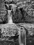A monochrome rendition contrasts the texture of hard rock and soft water flow in this study of Apikuni falls in Glacier National Park, Montana, USA