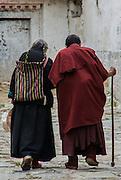China, Tibet, Shigatse, Thashilumpo Monastery, old woman and monk walking