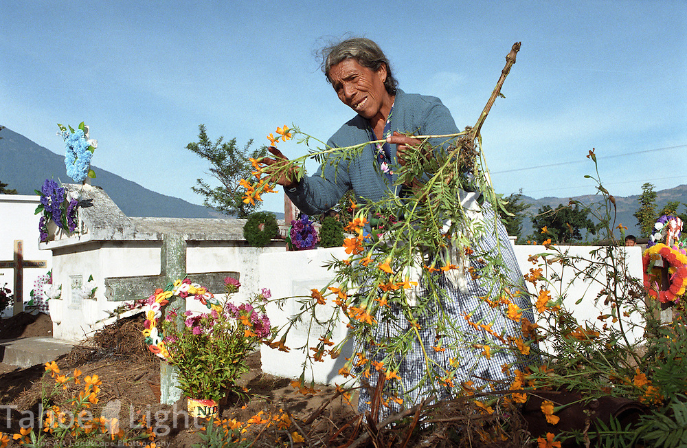 A woman decorates a grave at the cemetery in Guatemala City