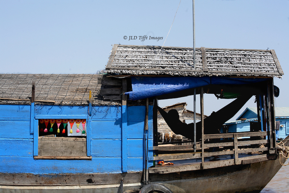 Side view of a floating boat home on Tonle Sap, showing the front porch on the bow, with the silhouette of a figure lying in a hammock