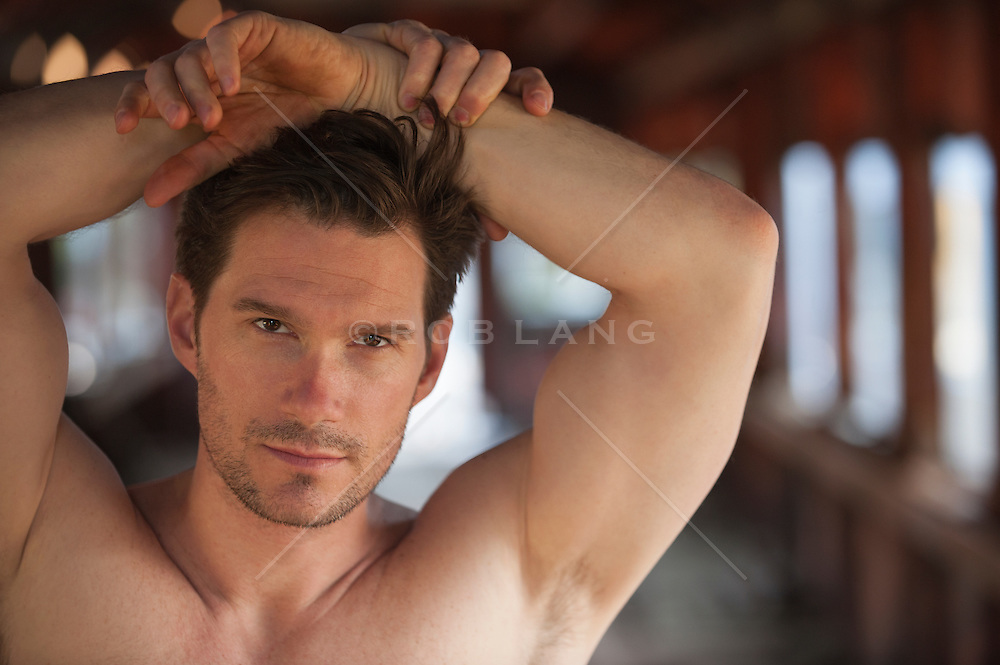 portrait of a rugged handsome shirtless man with his hands resting on his head
