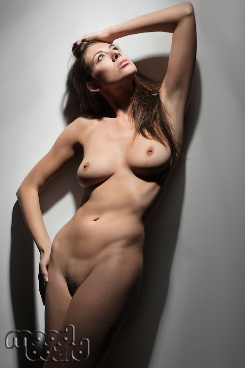 Sexy naked woman standing with hand in hair while looking up over colored background