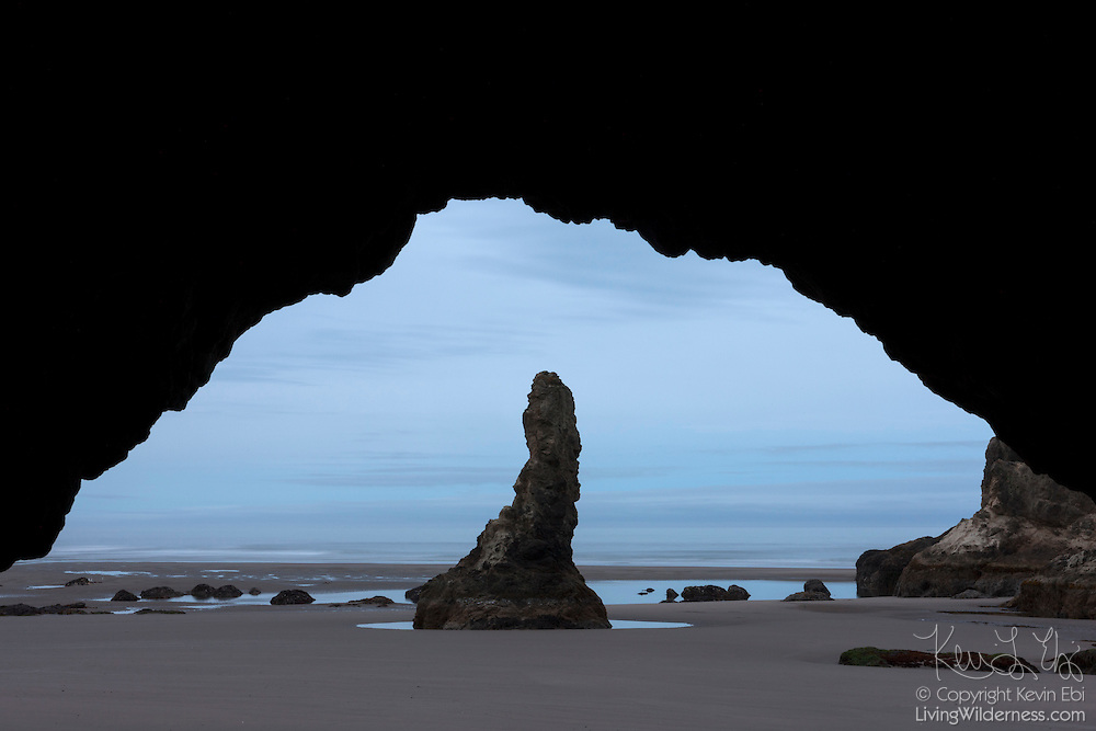 A tall sea stack, one of my rock formations on the Oregon coast at Bandon By The Sea, is framed by the opening to a sea cave.