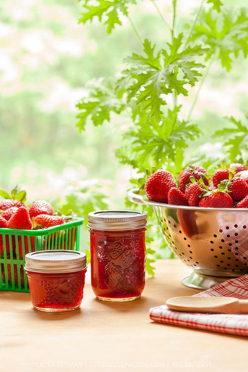 Fresh strawberries and strawberry jam in glass jam jars.